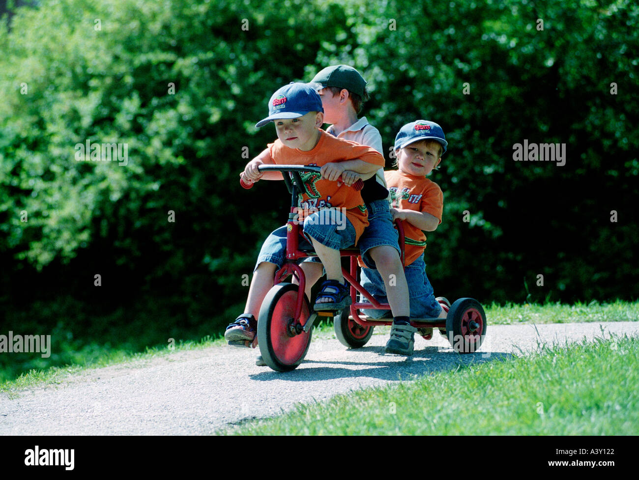 3 boys on a tricycle - Stock Image