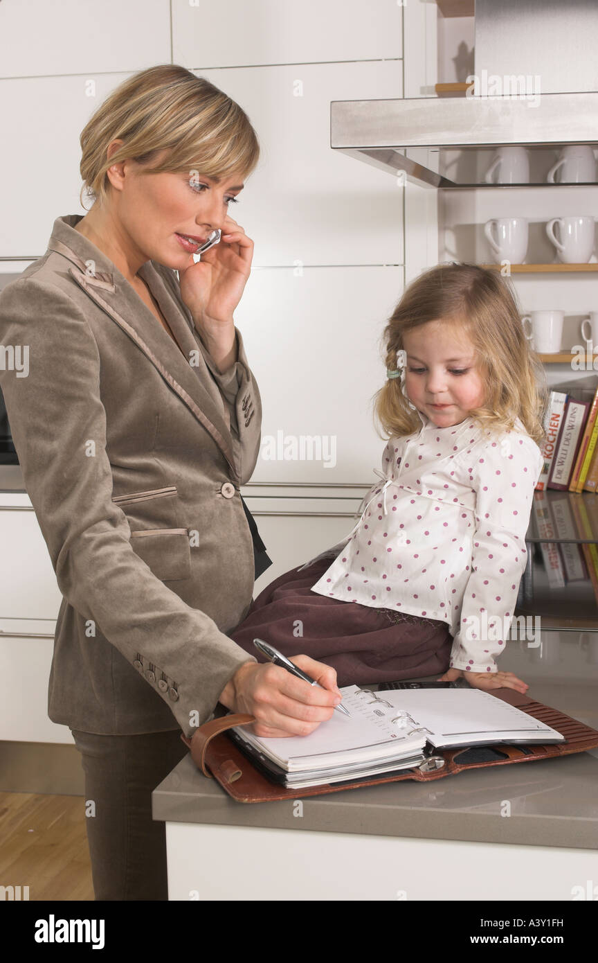 young businesswoman in kitchen looking at her daughter while listening to cellphone Stock Photo