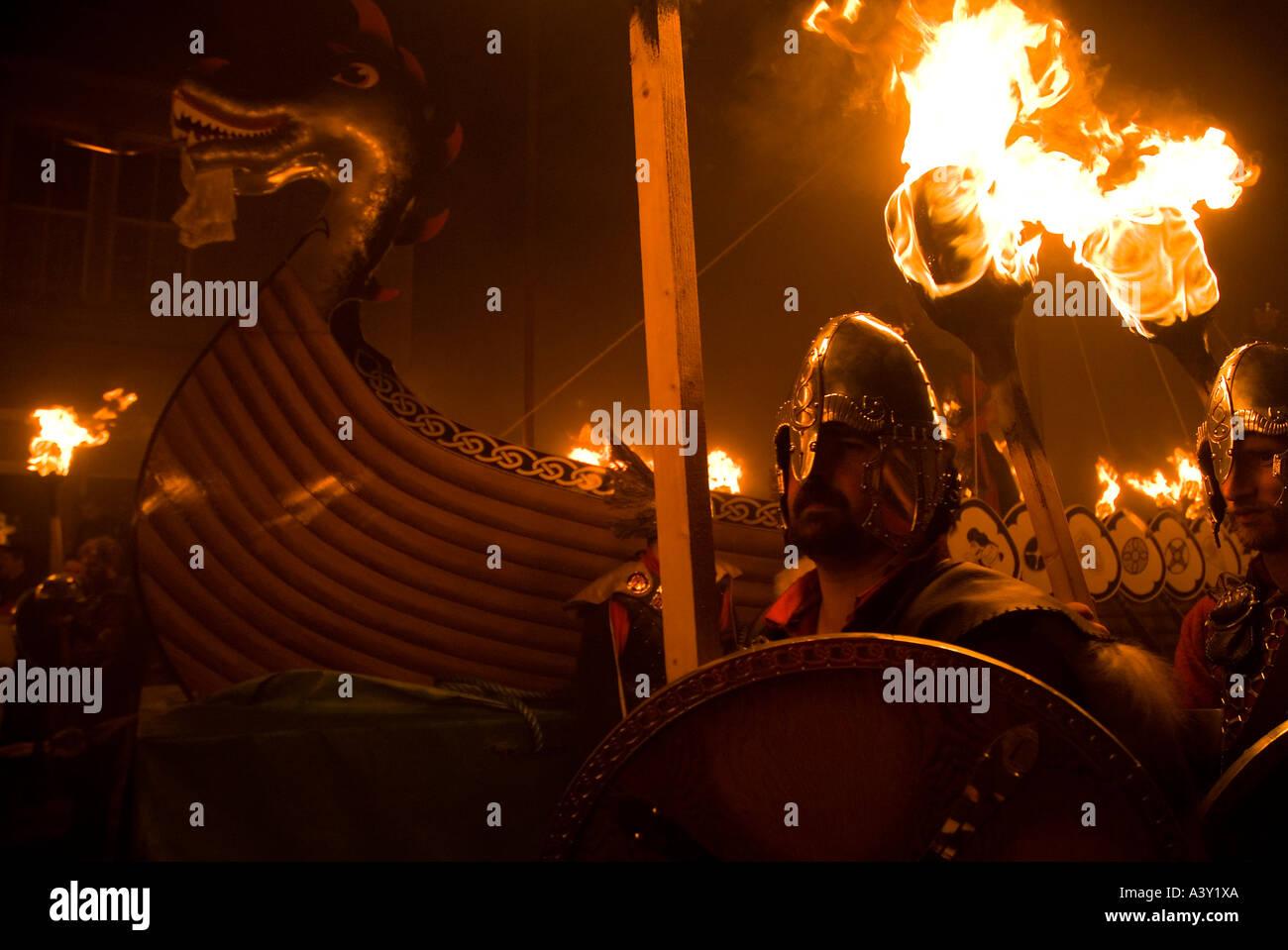 dh Up Helly Aa fire procession LERWICK SHETLAND Vikings escorting Viking longship galley festival parade - Stock Image