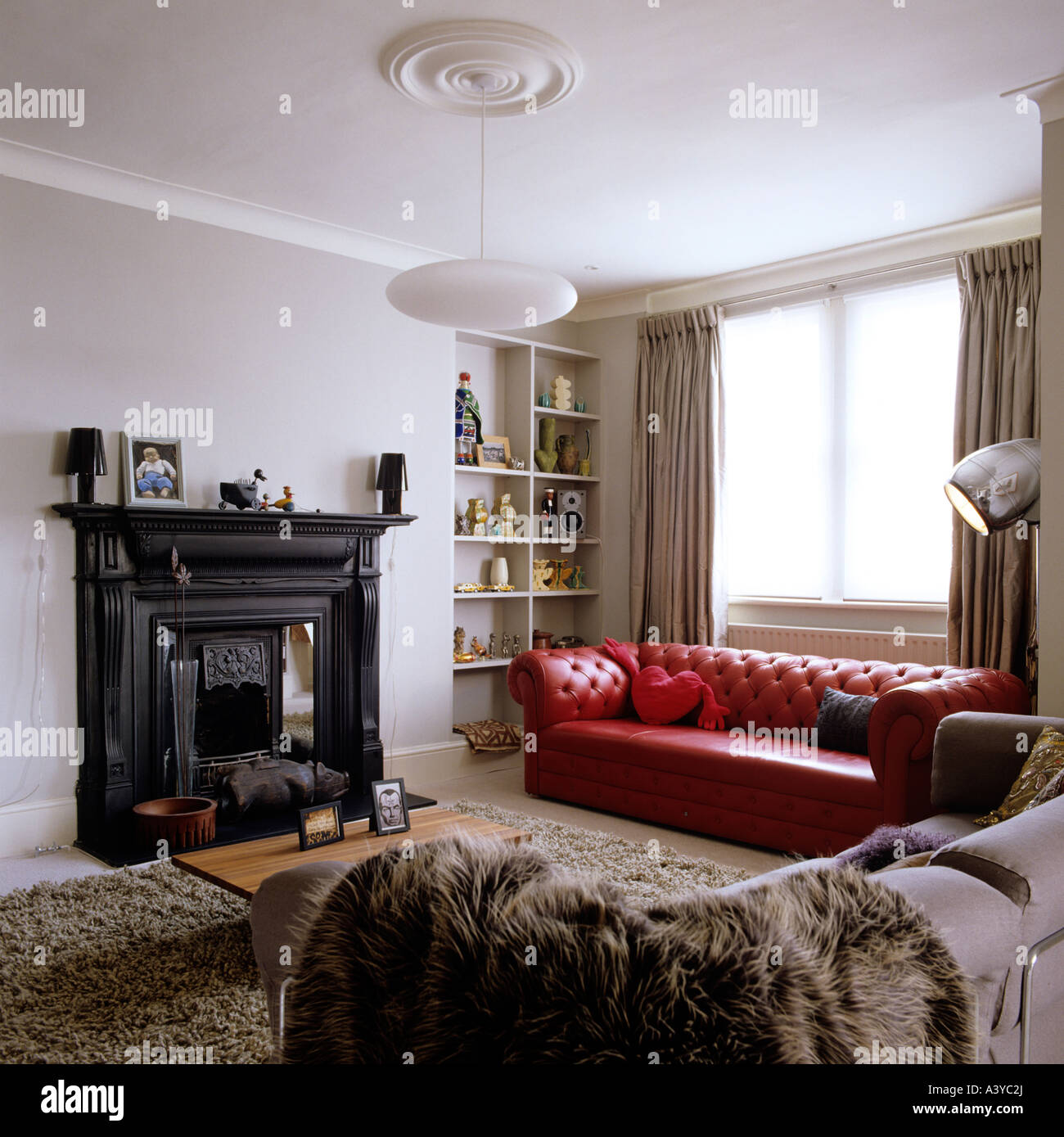 Living room with red leather sofa in contemporary London apartment ...
