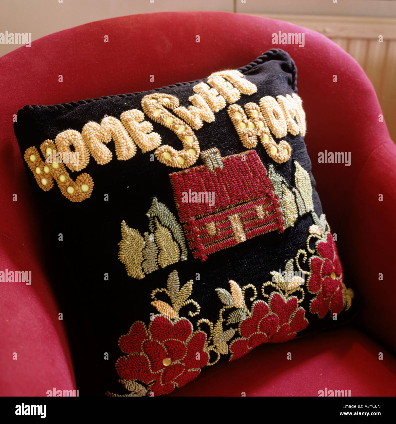 Hand-made cushion with writing Home Sweet Home on red armchair - Stock Image