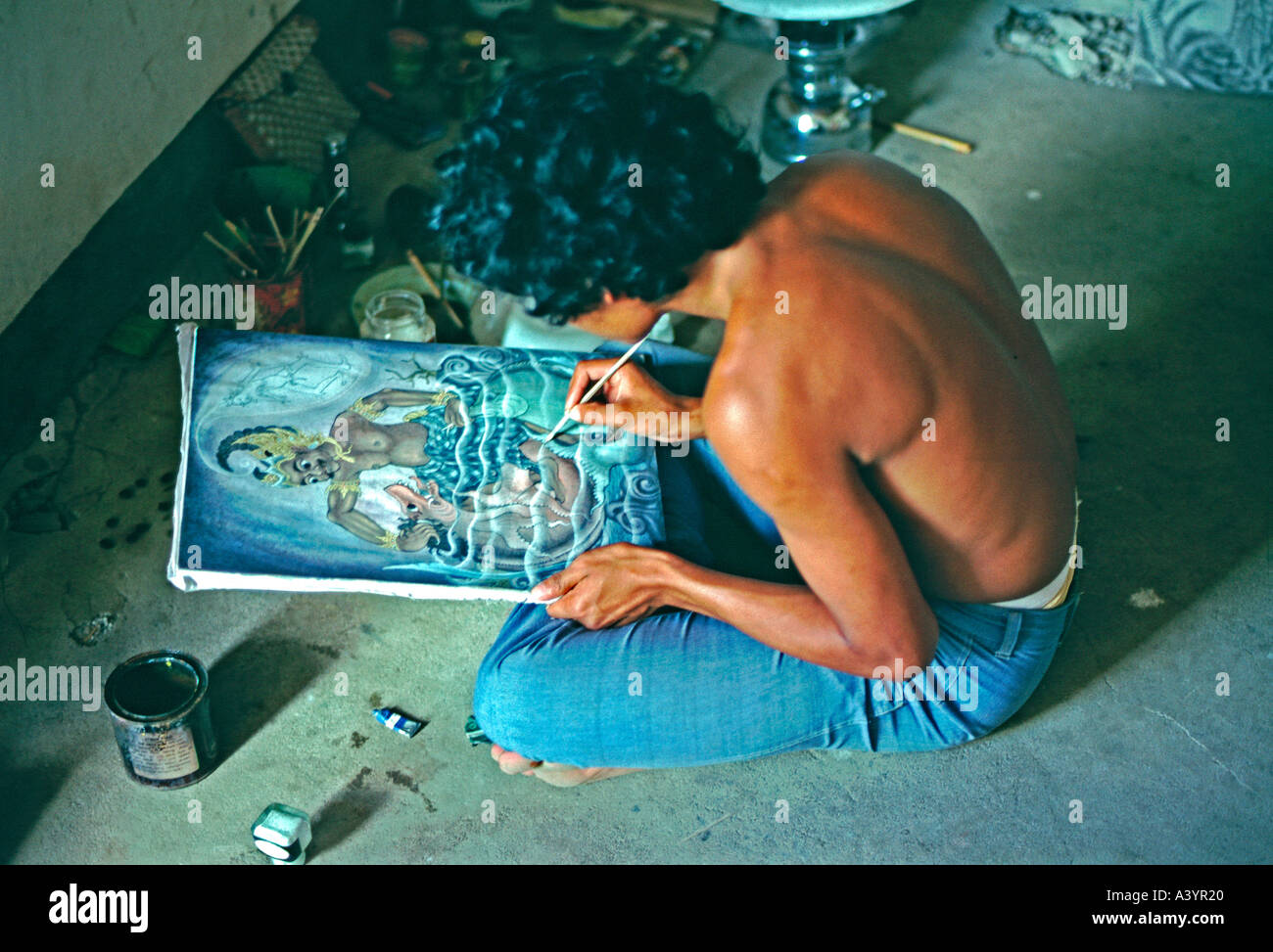 A Balinese artist in the artists enclave of Ubud works on a painting in traditional Balinese style - Stock Image