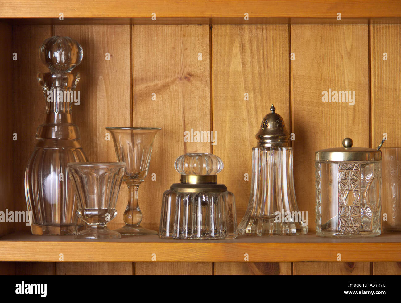 Antique glass on a wooden shelf - Stock Image