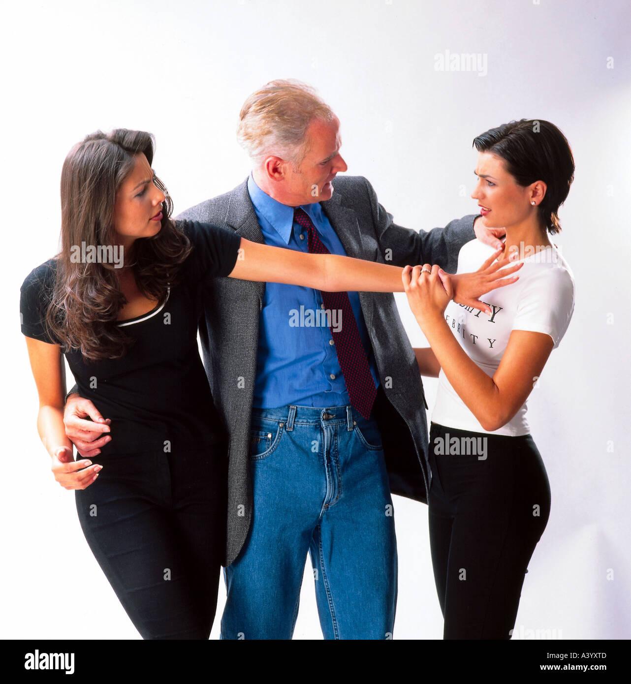 man flirting with two women jealousy - Stock Image