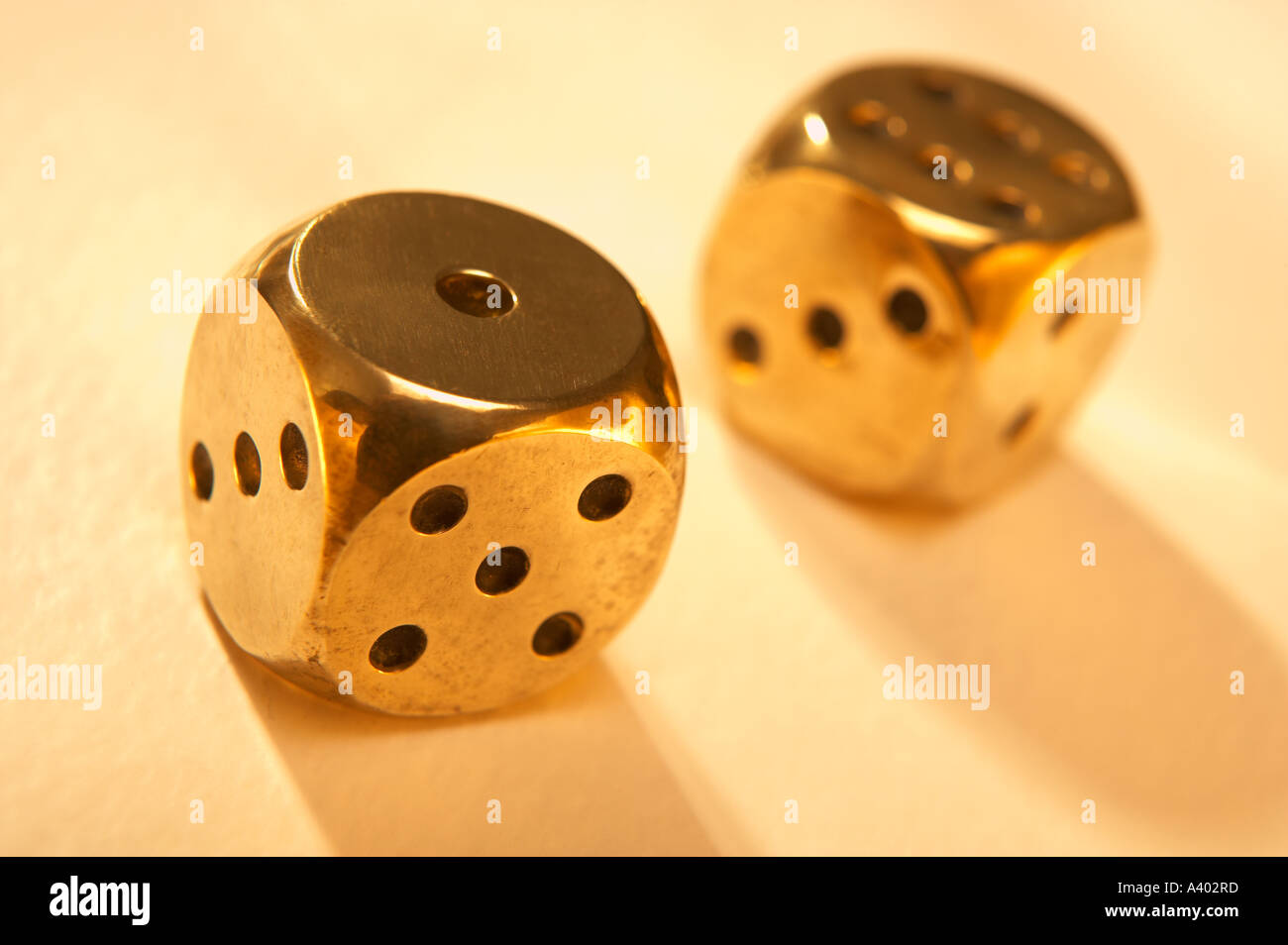 TWO ANTIQUE POLISHED GOLD BRASS DICE - Stock Image