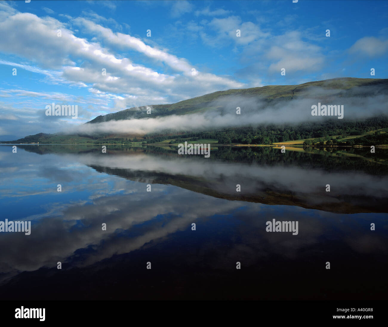 Early morning mist lies along the hill slopes on the north shore of Loch Leven seen from Invercoe Glencoe Scottish Highlands - Stock Image