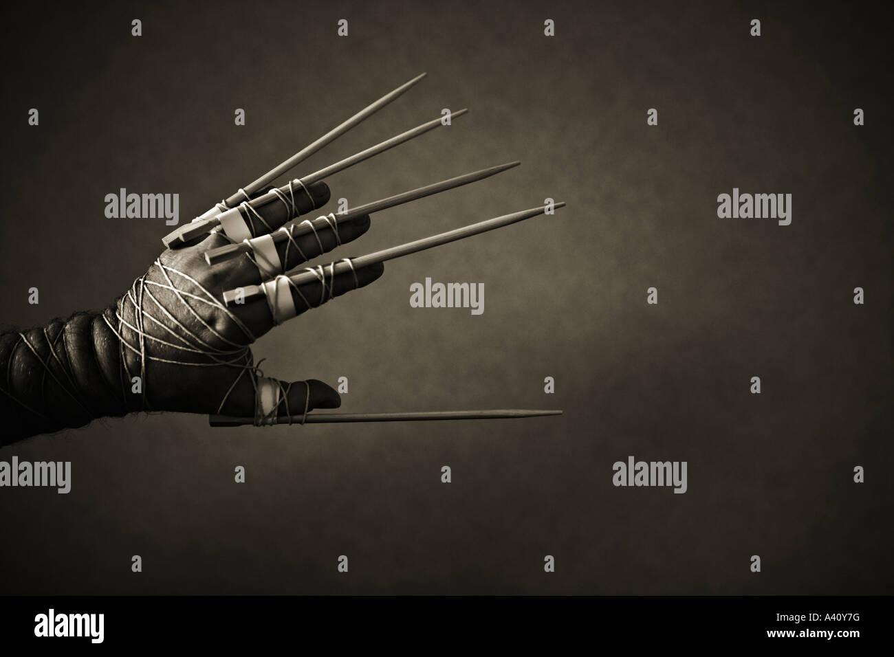 Man's hand with chop sticks tied to fingers - Stock Image
