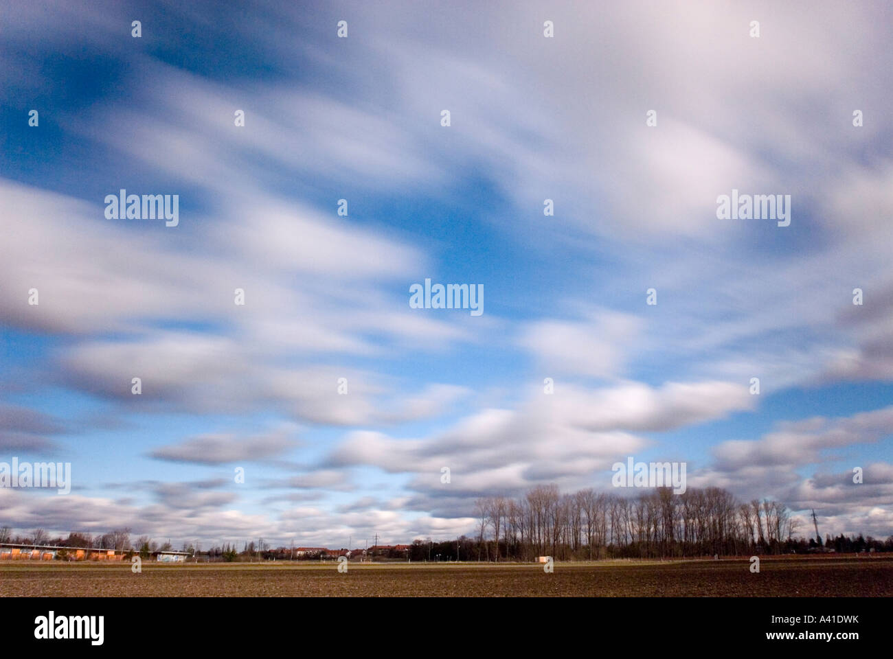 wintry landscape with field and bleak small wood and white clouds blurred while drifting near Munich Bavaria Germany - Stock Image