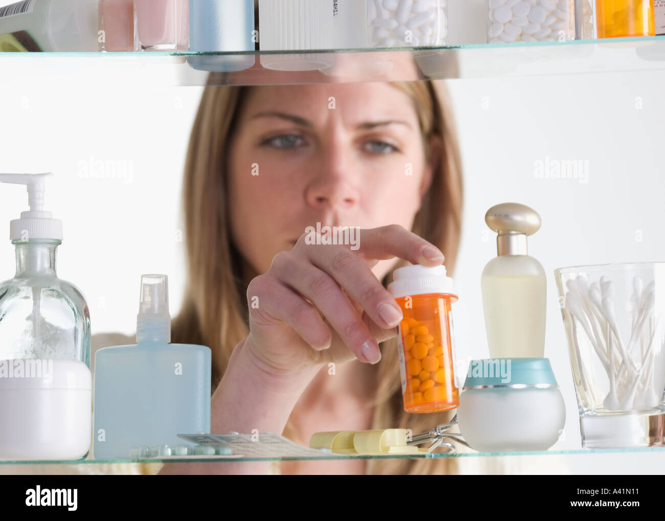 Woman removing medicine from cabinet - Stock Image