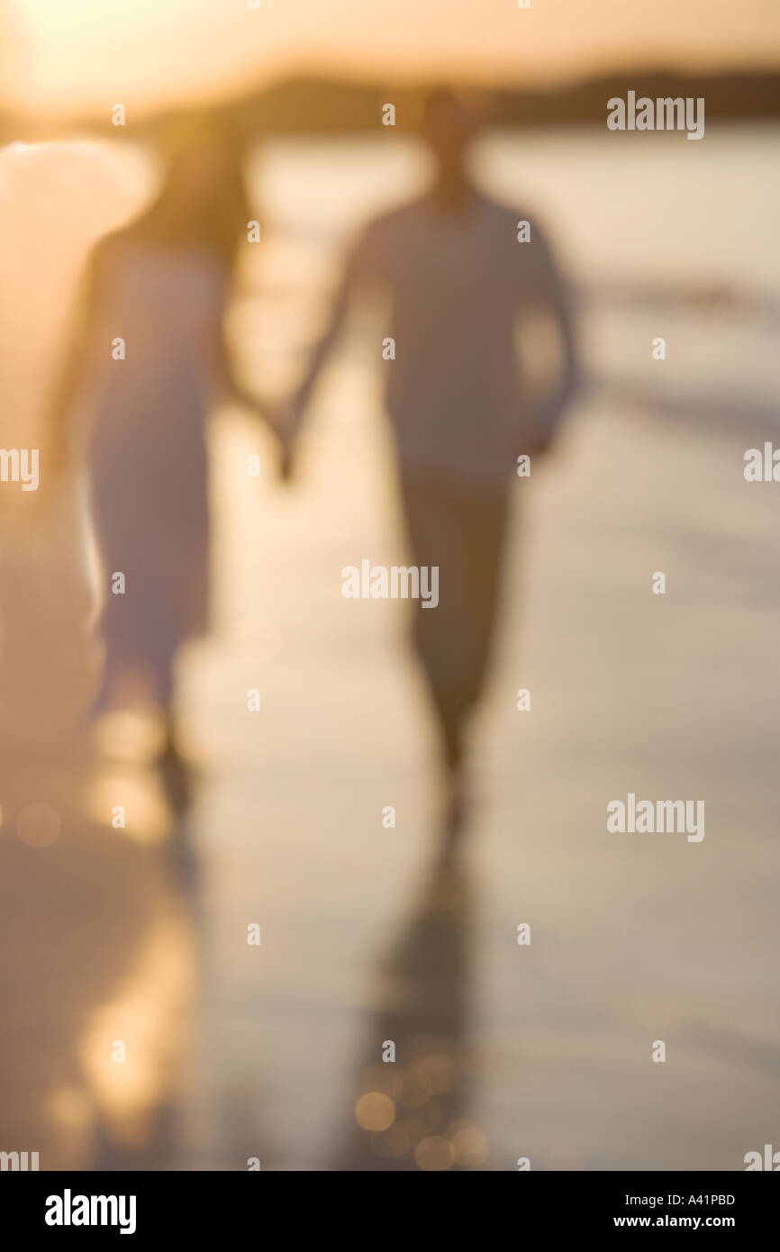 Couple strolling on a beach - Stock Image