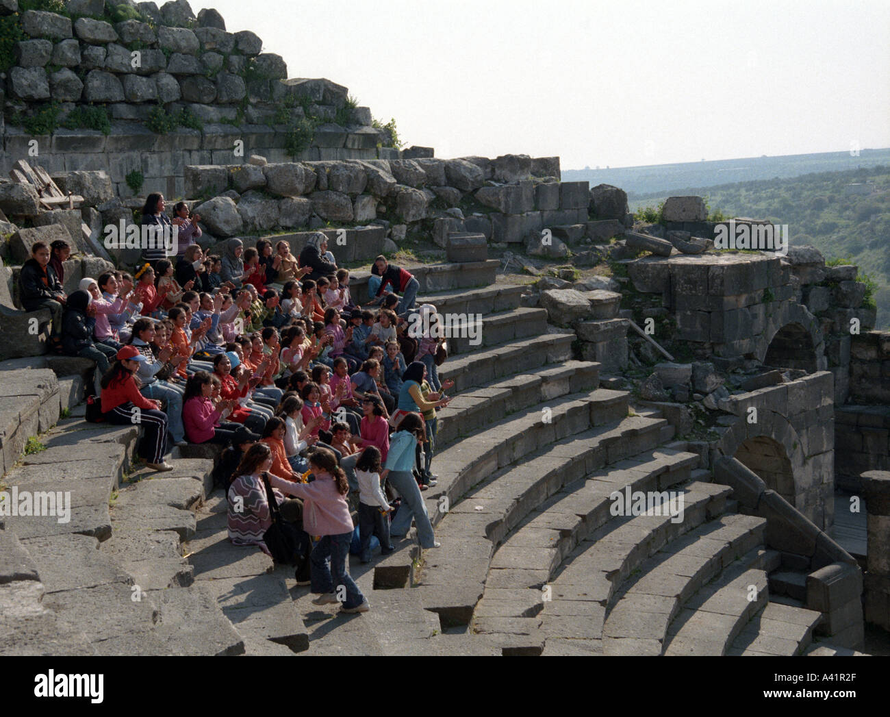 Schoolgirls singing at the West Theatre Umm Qays Jordan - Stock Image