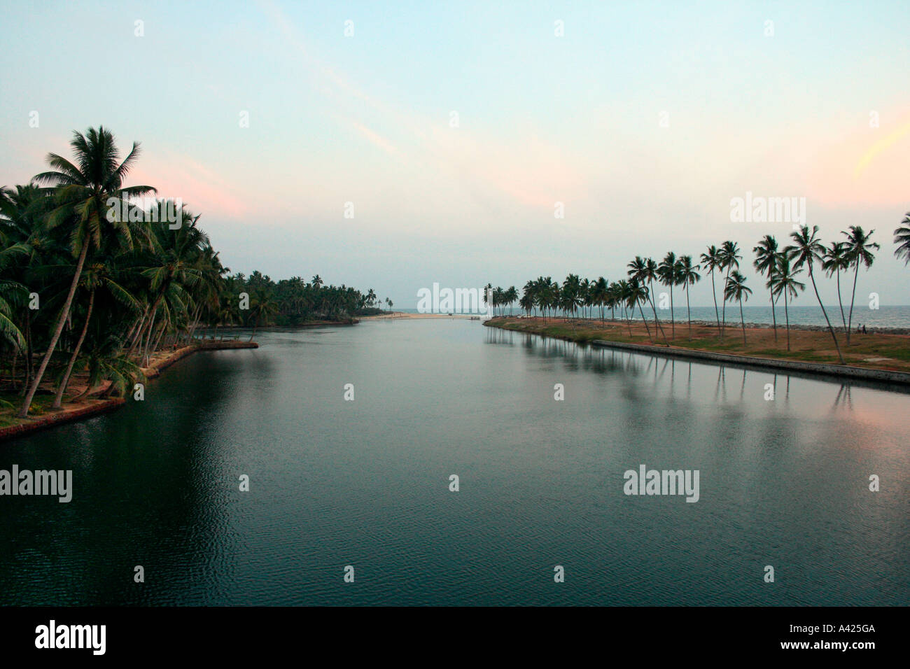 Back waters of Kerala with coast and coconut trees outlined against evening sky - Stock Image