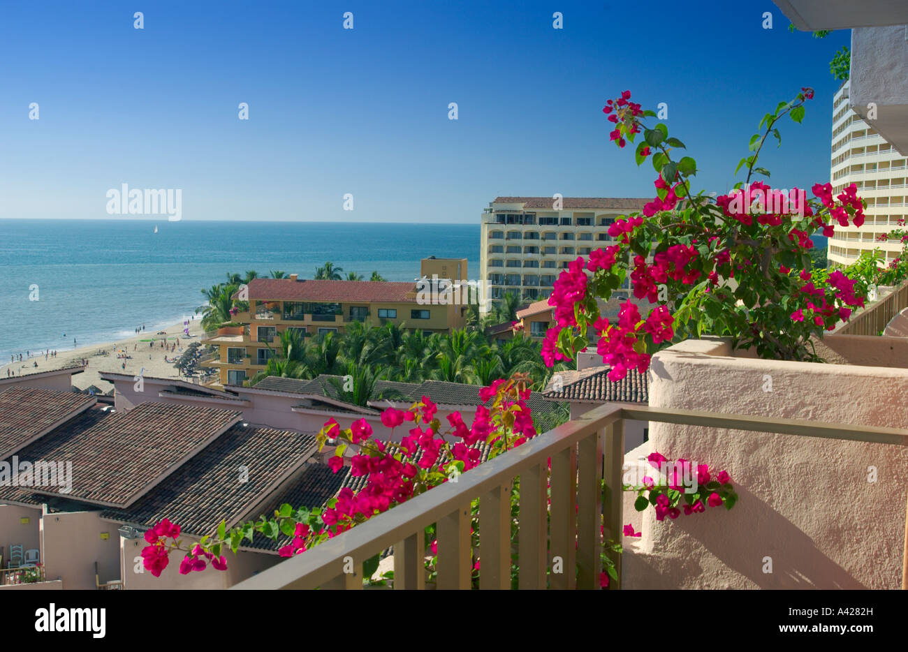 A hotel balcony decorated with red bougainvillea flowers in Puerto Vallarta Mexico - Stock Image
