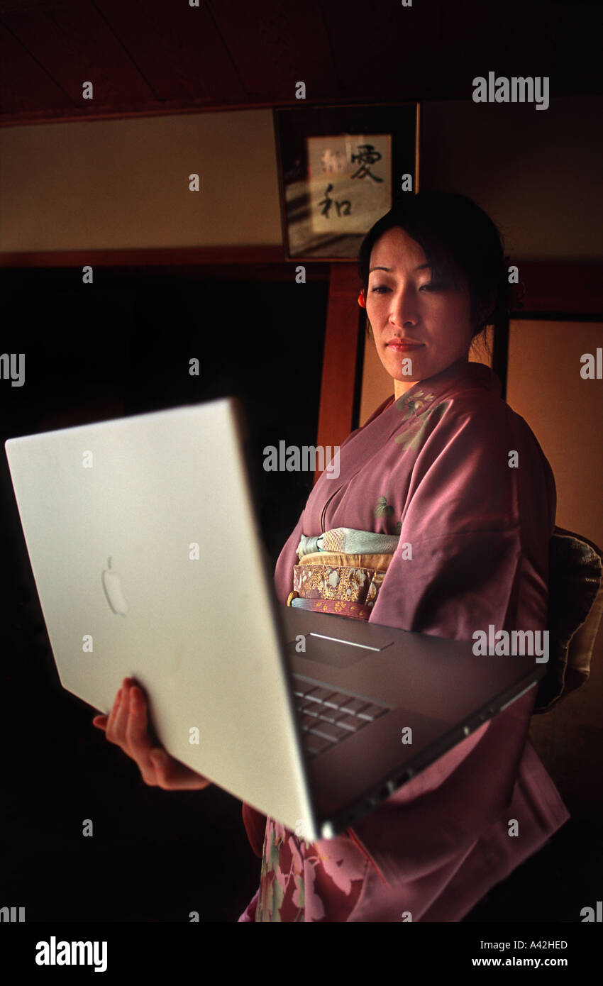 Japanese woman wearing a colourful silk kimono and holding a powerful laptop computer Nara prefecture Japan - Stock Image