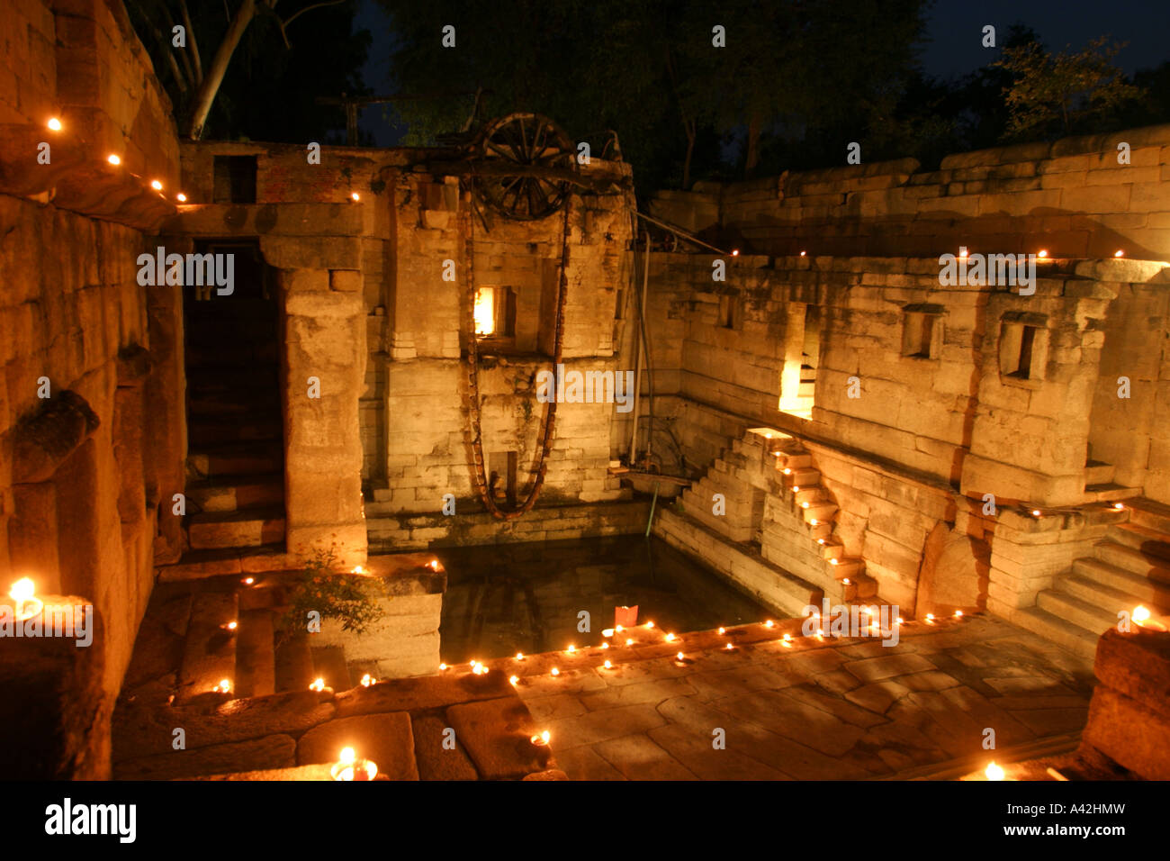 Ancient water well illuminated with oil lamps at Narlae in Rajasthan, India - Stock Image