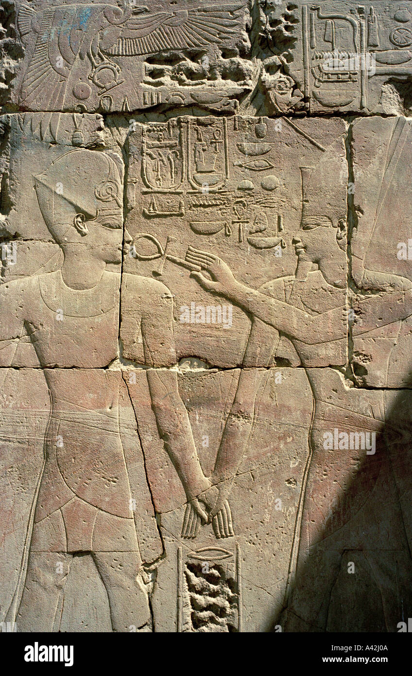 The god Amun and the Pharaoh hold hands while by touching his nose with the Ankh the god is bestowing eternal life on Pharaoh - Stock Image