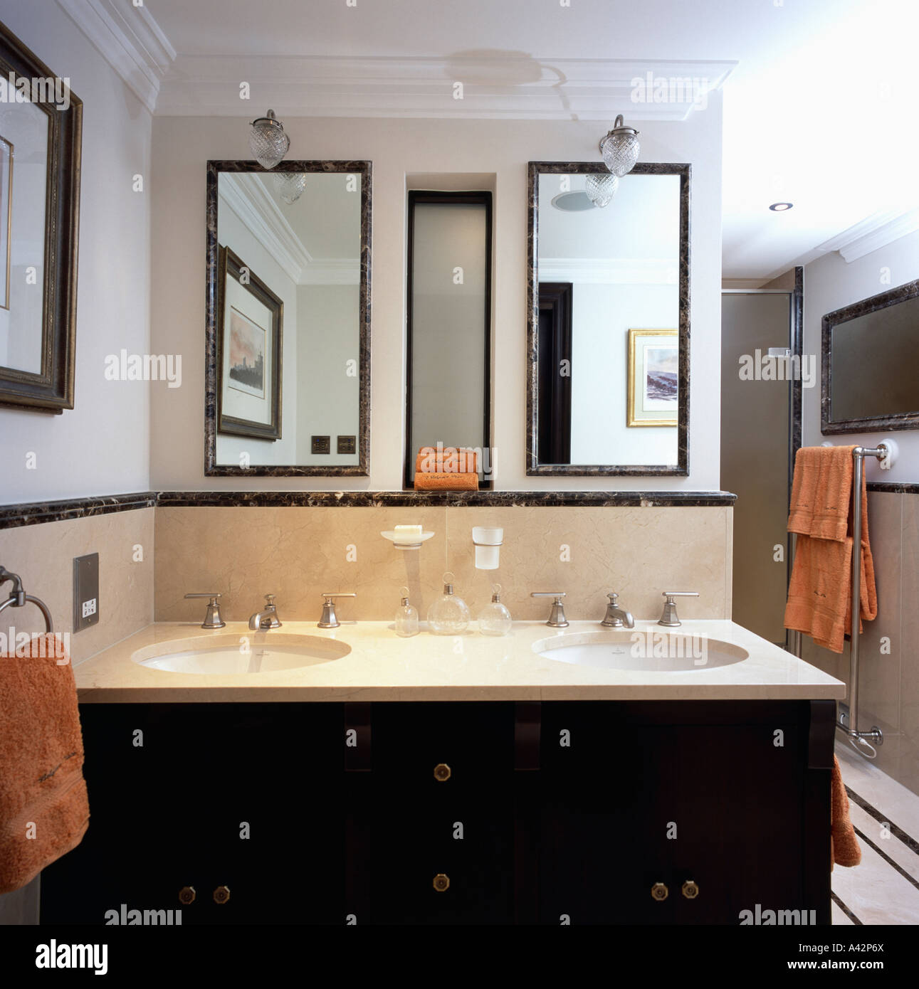 Mirrors above double basins set into vanity unit in modern bathroom - Stock Image