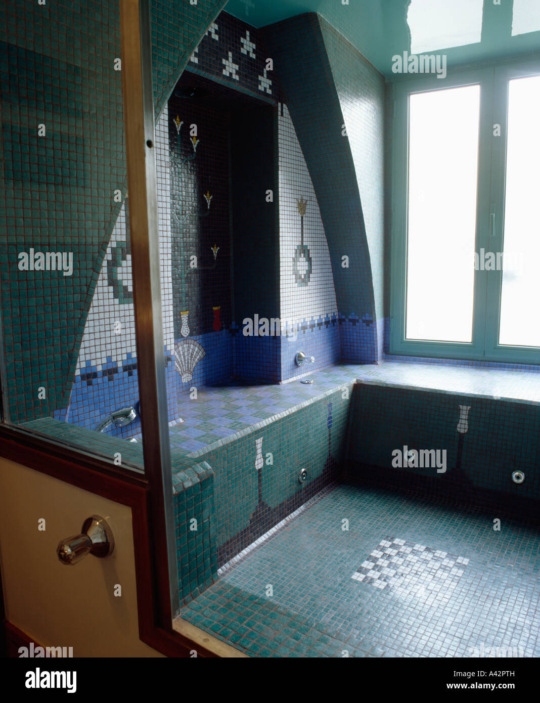 Green tiled sunken bath in blue and green bathroom Stock Photo ...