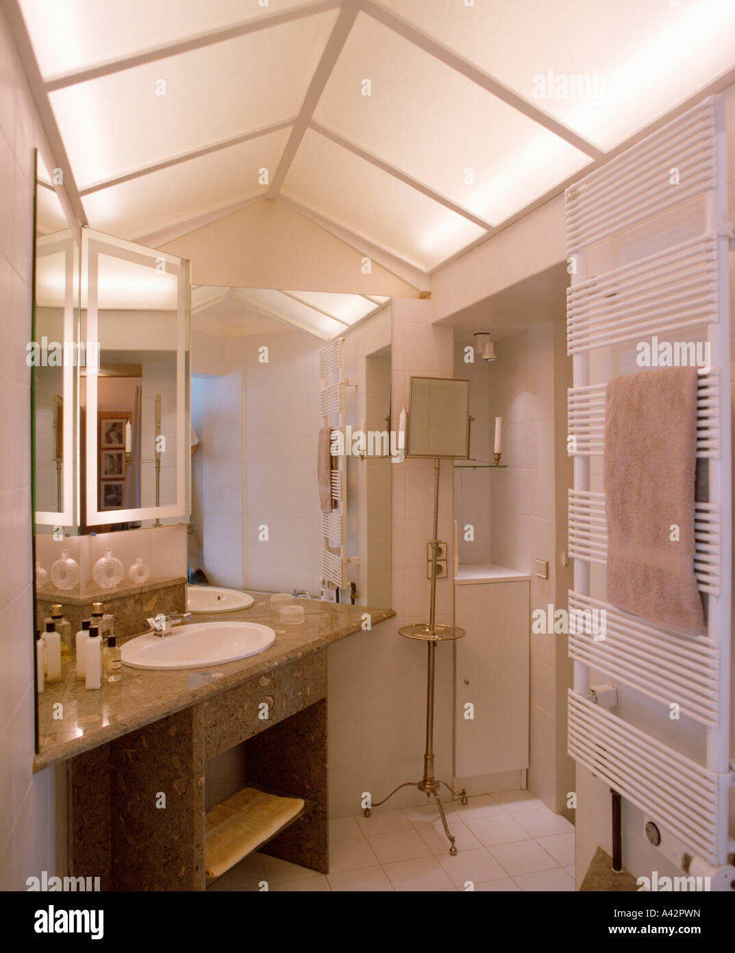 Glass panelled ceiling in white bathroom with radiator and basin in vanity unit - Stock Image