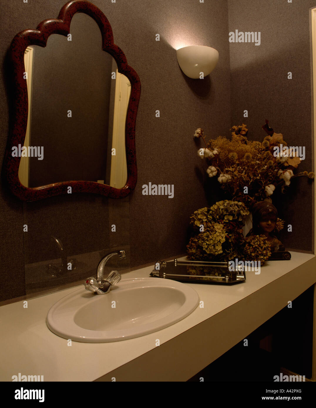 Mirror above basin in vanity unit and wall light in brown bathroom - Stock Image