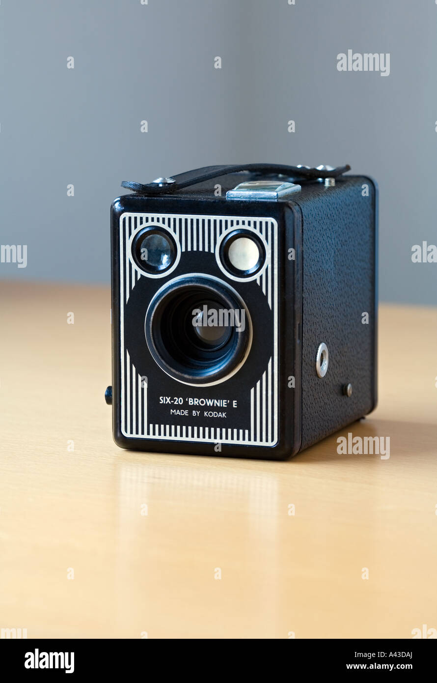 Vintage Kodak Box Brownie camera studio shot on a clean, shiny, reflective birch wood table and clean grey background. - Stock Image