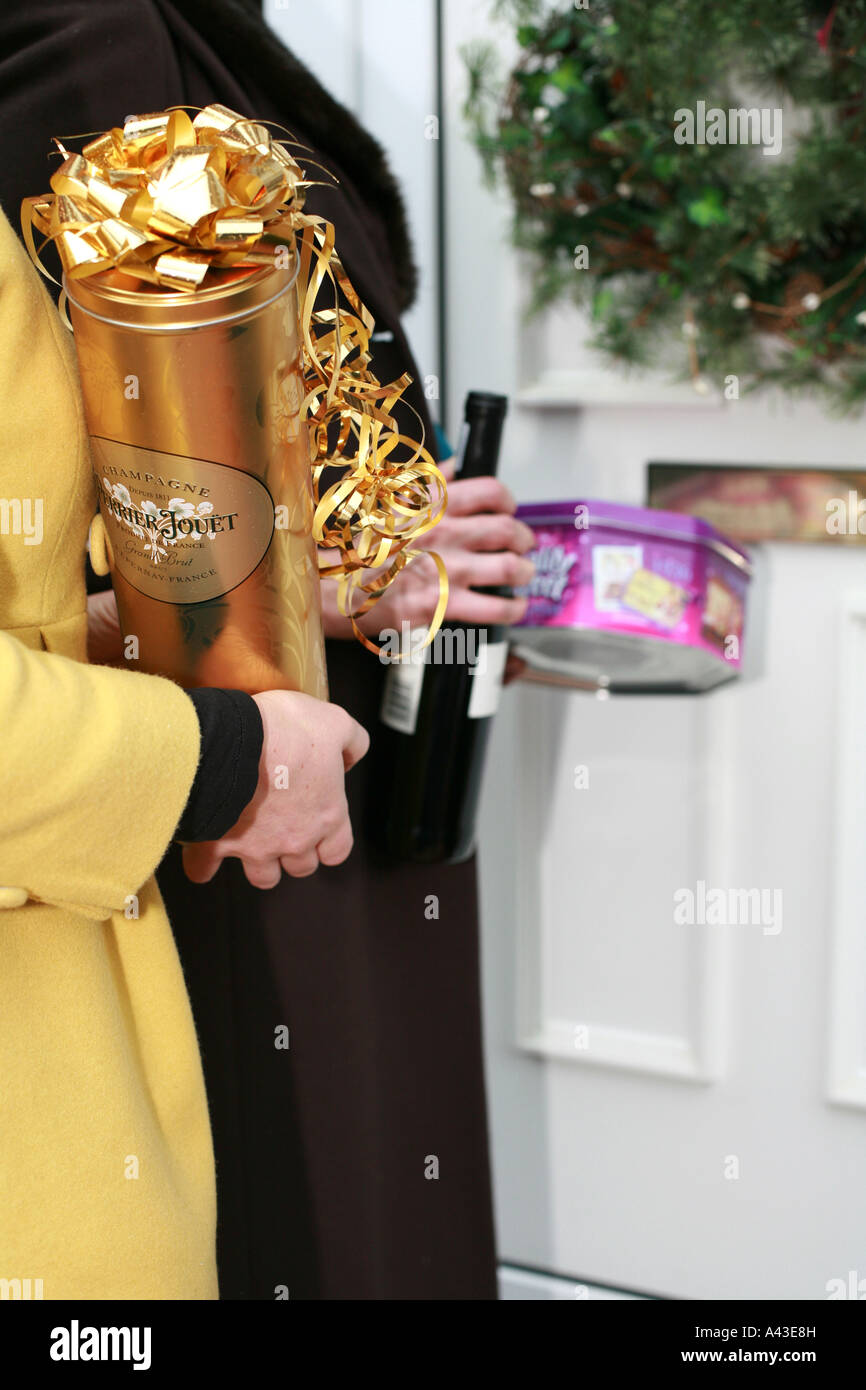Guests arrive at the front door of a house carrying season gifts of sweets and alcohol for a house party at Xmas - Stock Image