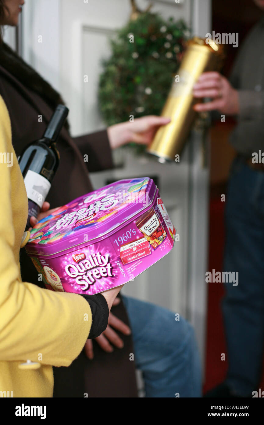 Guests arrive at the front door of a house carrying gifts for a house party at Xmas Christmas and are greeted by - Stock Image