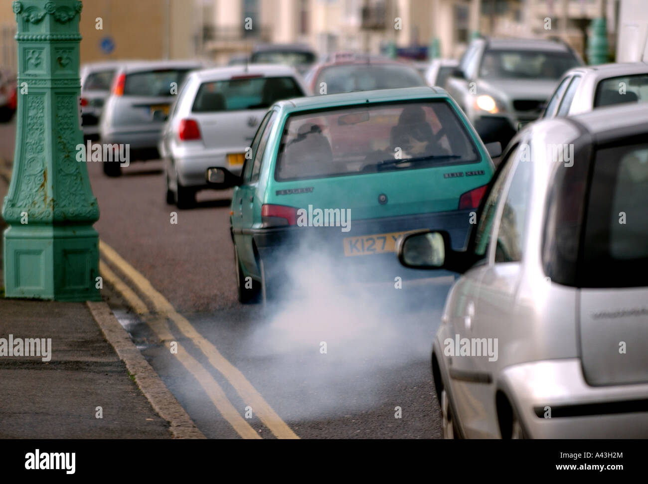 A Car Billows Out Exhaust Fumes As It Drives In Traffic Along Stock