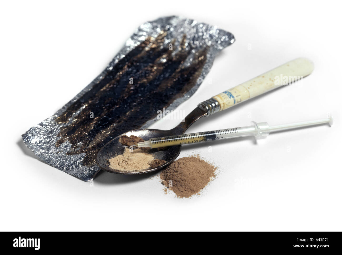 Heroin photographed on a white background showing the equipment necessary to prepare the powder for injection. - Stock Image