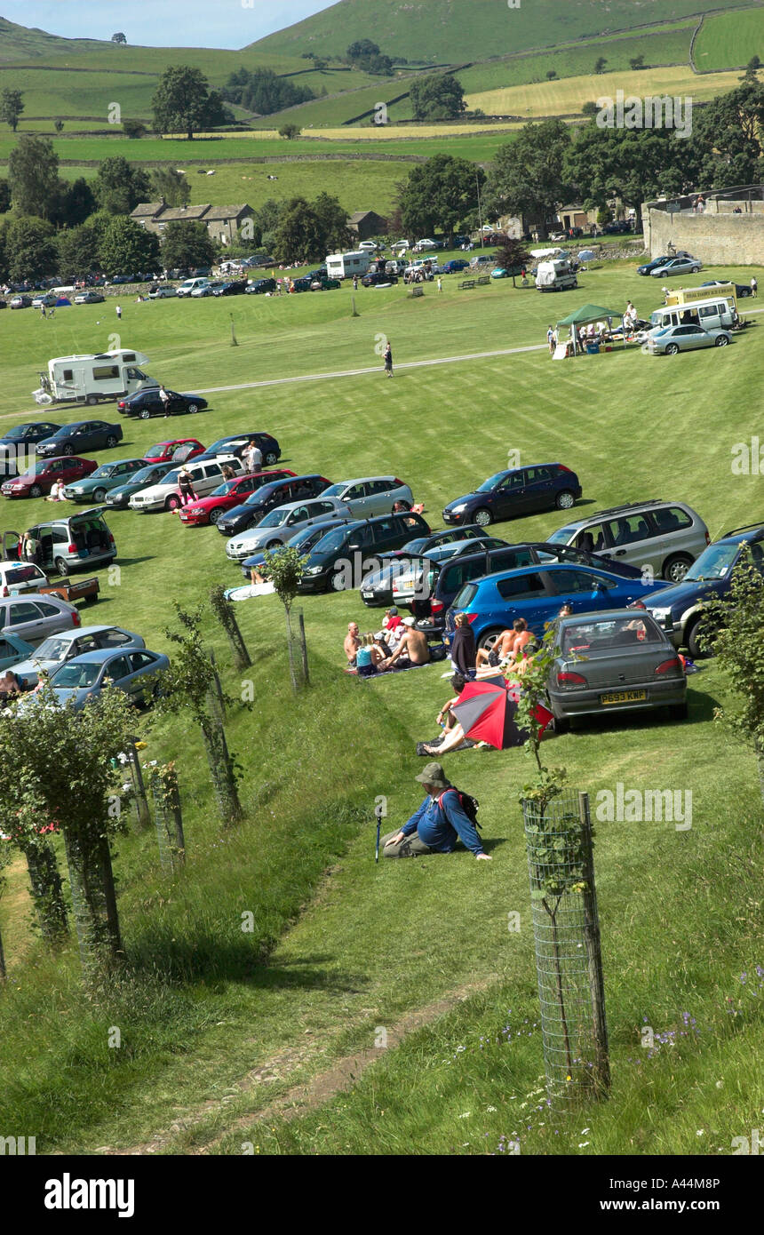 Car park in field by riverside near Burnsall, Yorkshire Dales, England Stock Photo
