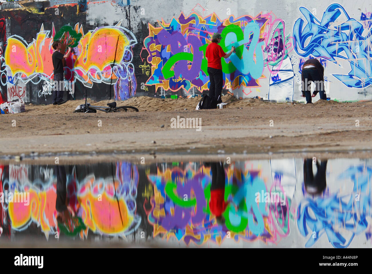 Young Graffitti artists painting a wall on disused land - Stock Image