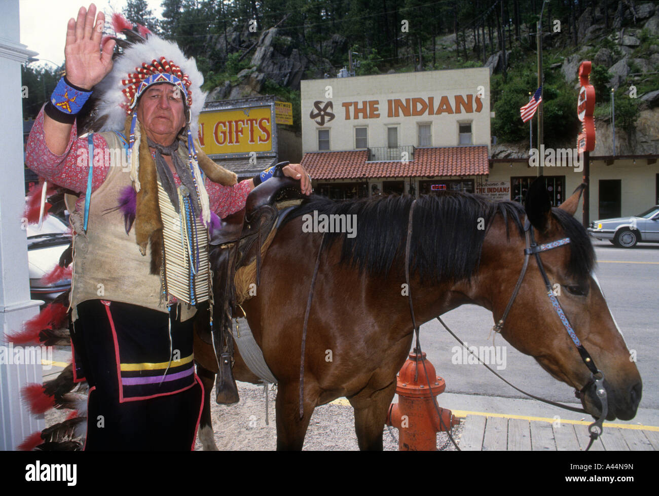 A Native American  Indian Earns A Few Bucks, By Posing For Tourist Photographs In The South Dakota Town Of Keystone. - Stock Image