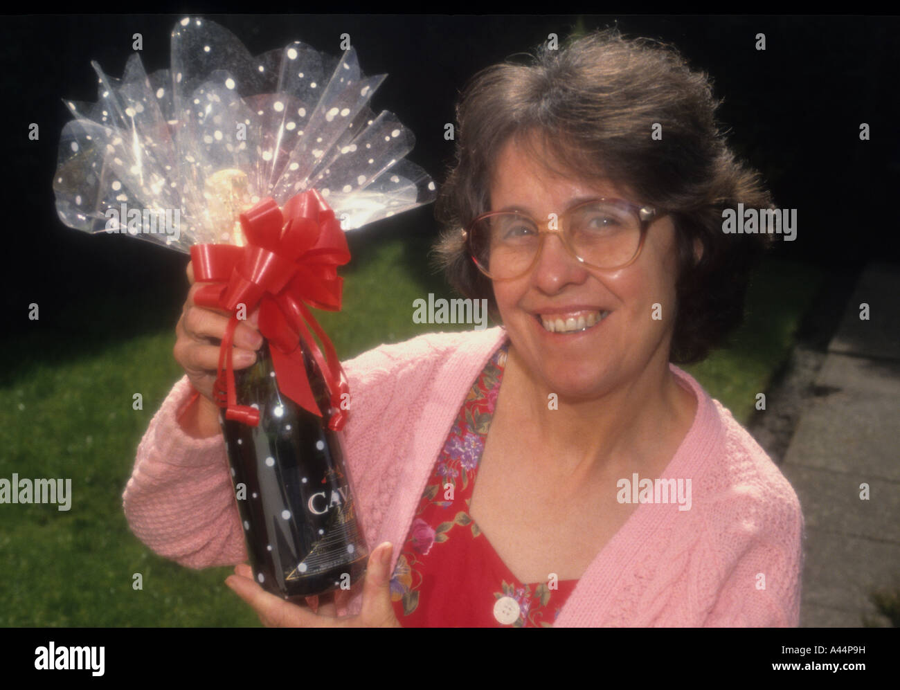 Healthy Happy Middle Aged Woman Holding A Given Gift ,Of A Bottle Of Champaign. - Stock Image