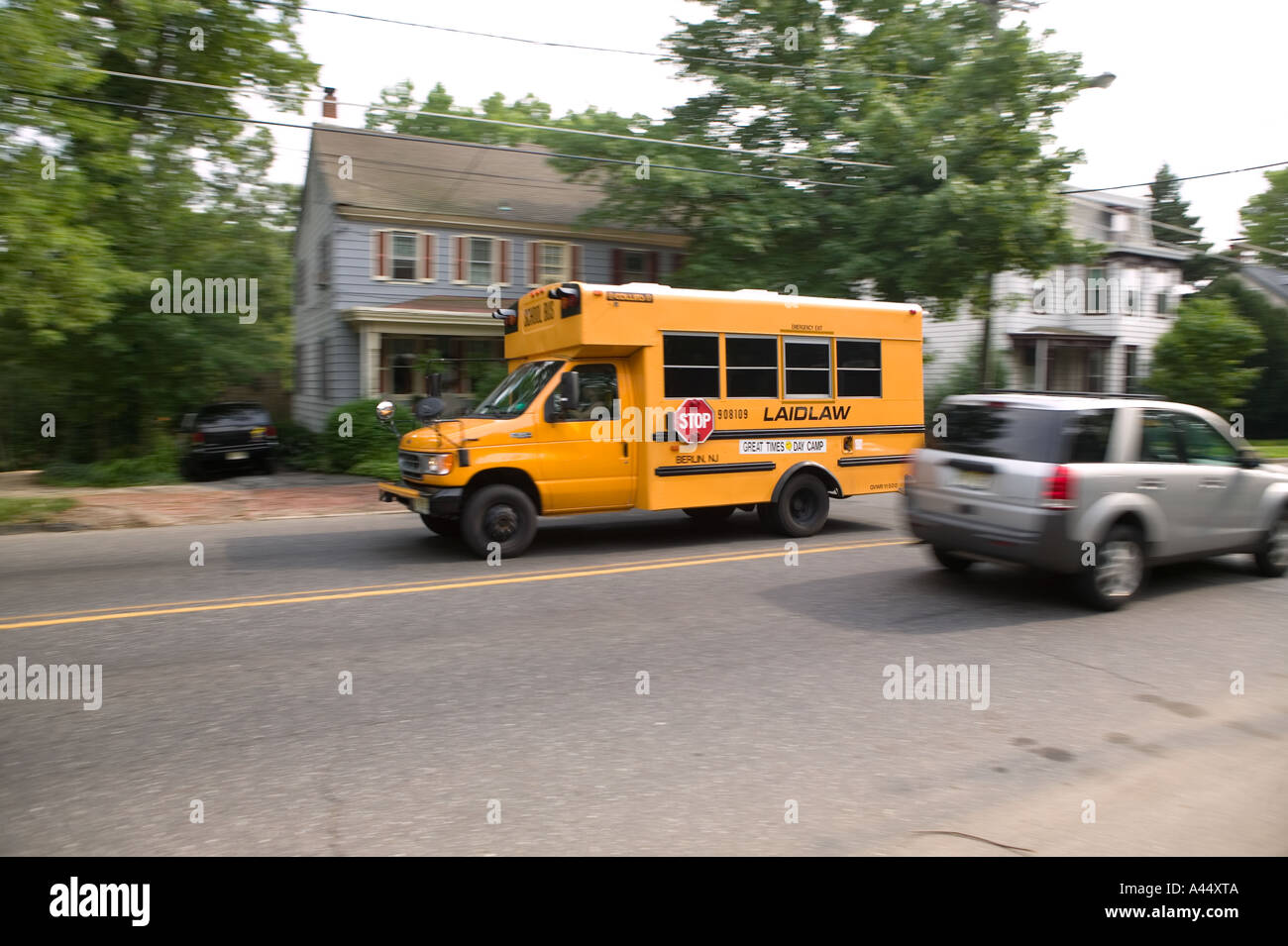 A short yellow school bus drives through the town of
