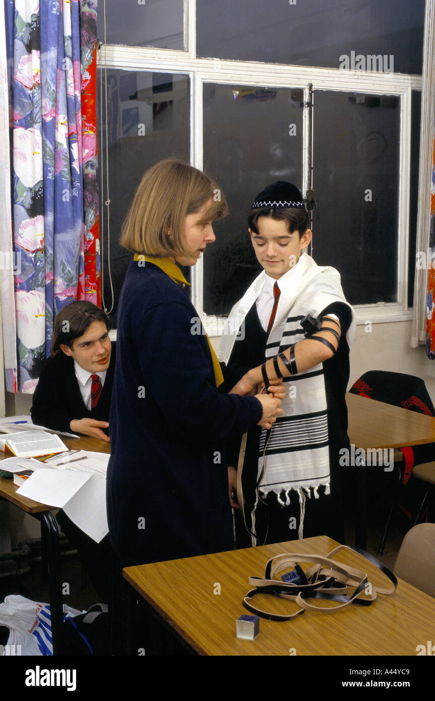 teacher dressing pupil with ancient jewish costumes at religious education lesson redbourne upper school bedfordshire - Stock Image