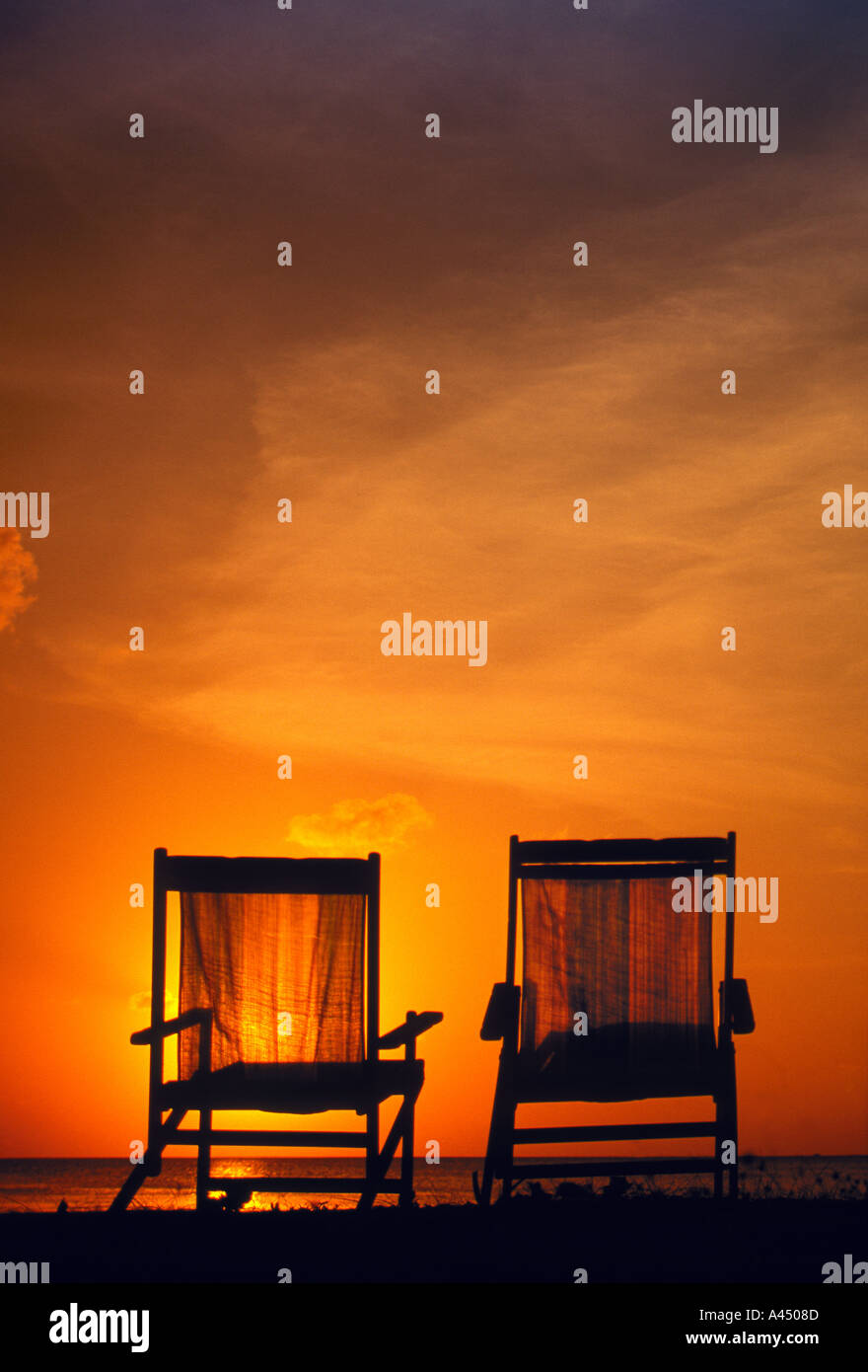 two beach chairs in sunset - Stock Image