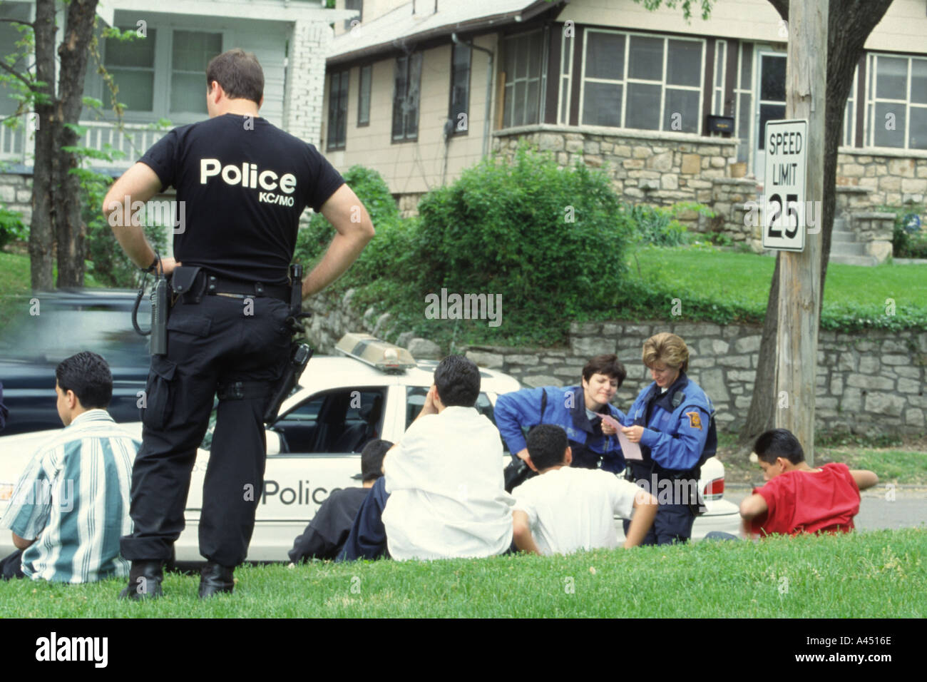Police officer with a group of suspected gang members. Kansas City, MO, PD, USA. Street Narcotics Unit TAC team. - Stock Image