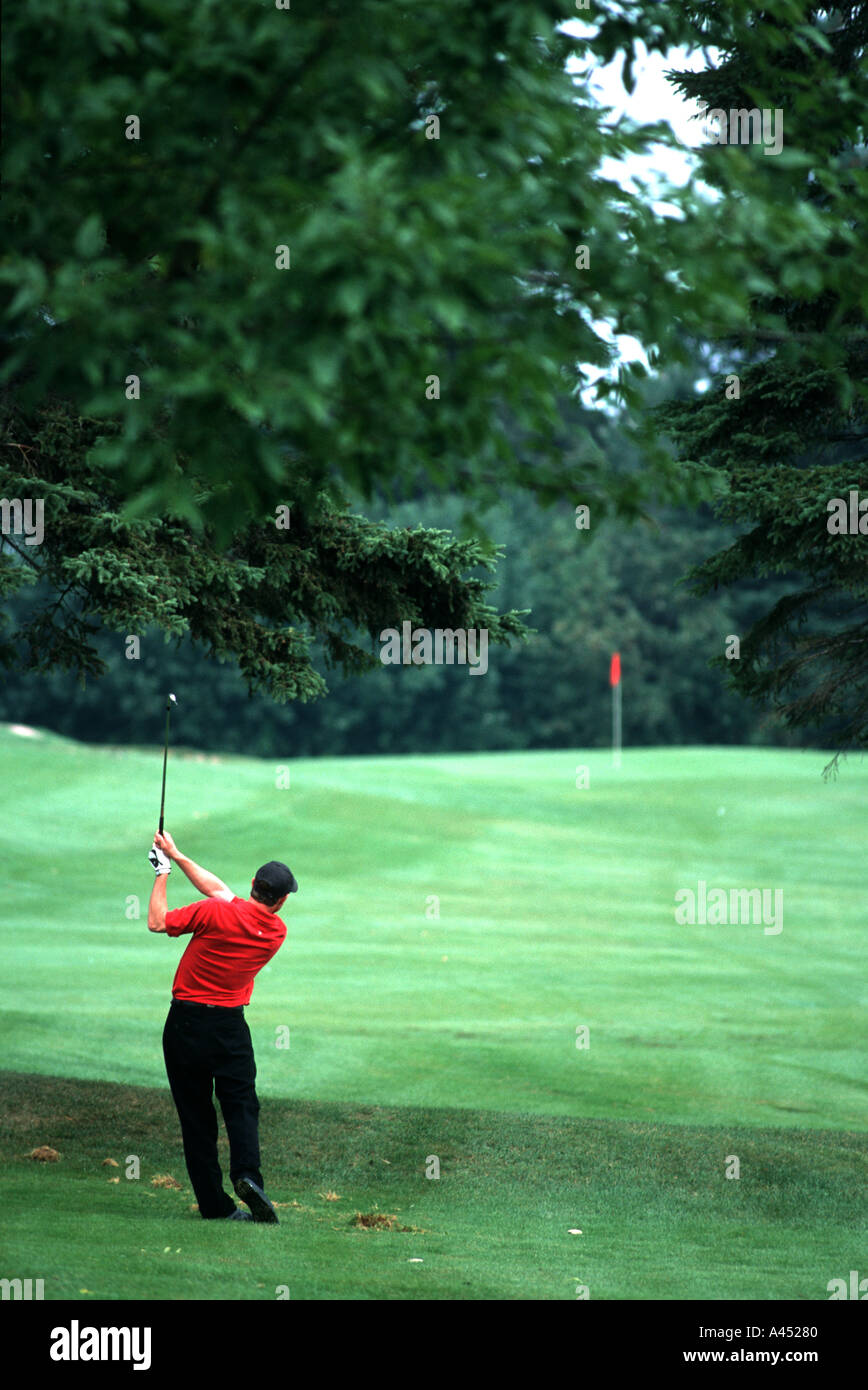 golfer hitting an approach shot in New Brunswick Canada - Stock Image