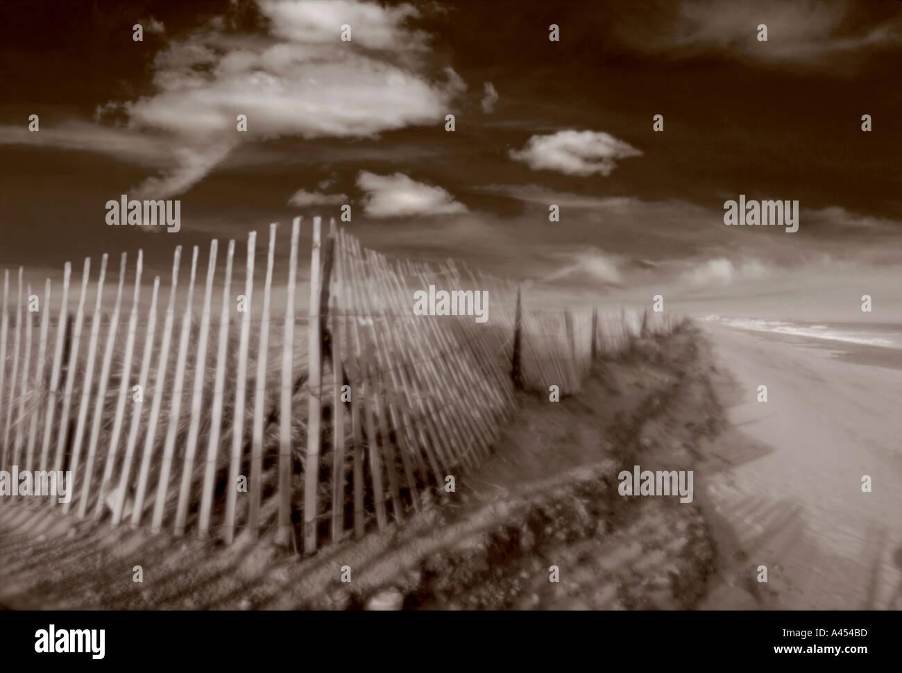 Horizontal Sepia toned image of fence on sand dune along beach - Stock Image