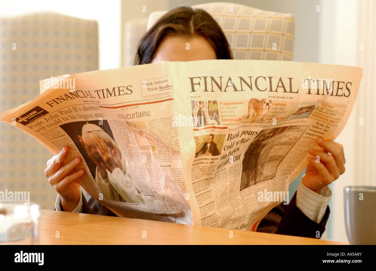 British business woman reading Financial Times London UK looking at good or bad news about the credit crunch and recession. Stock Photo