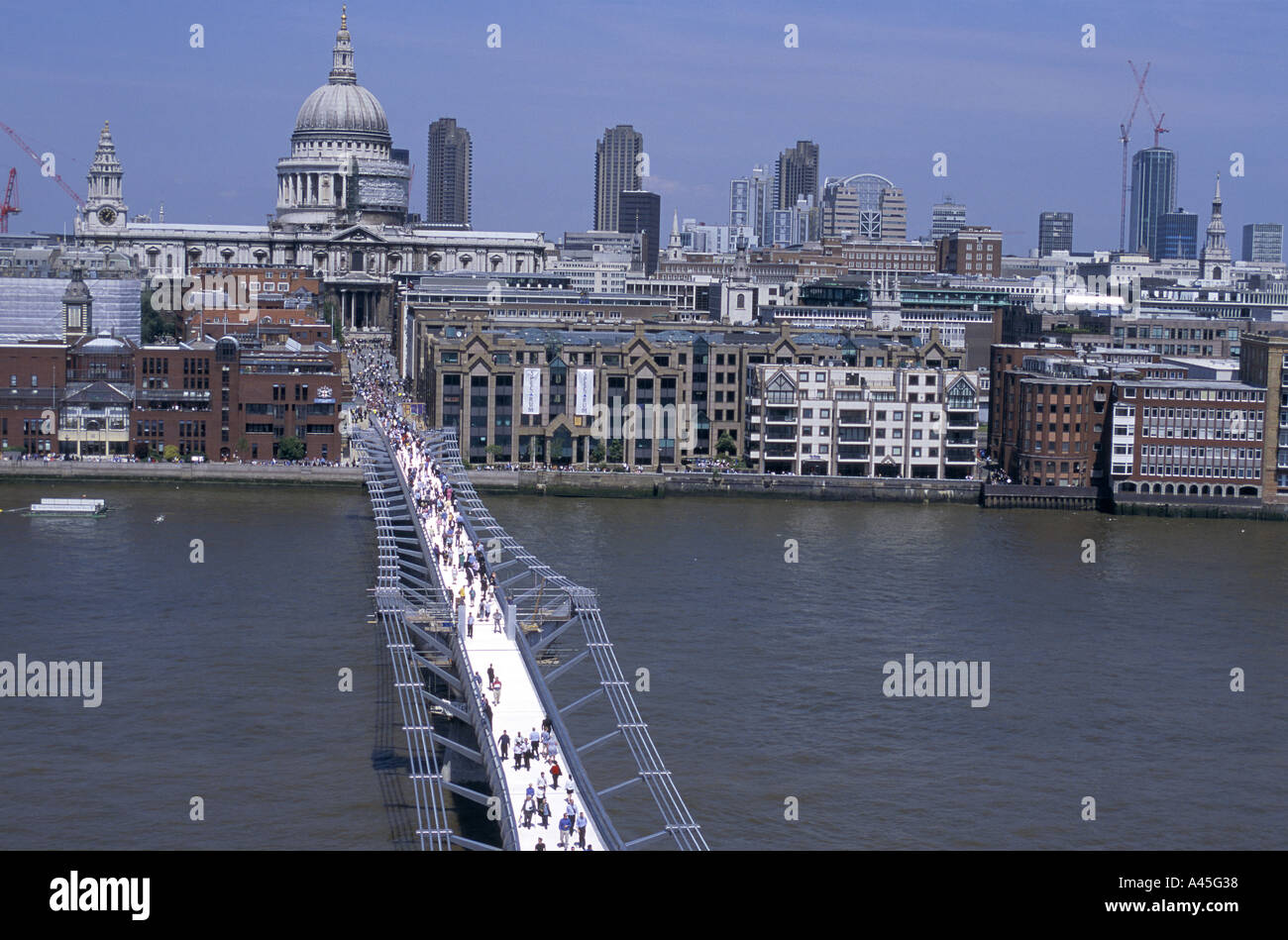 pedestrian on millennium bridge stretching from st pauls cathedral to tate modern over river thames london Stock Photo