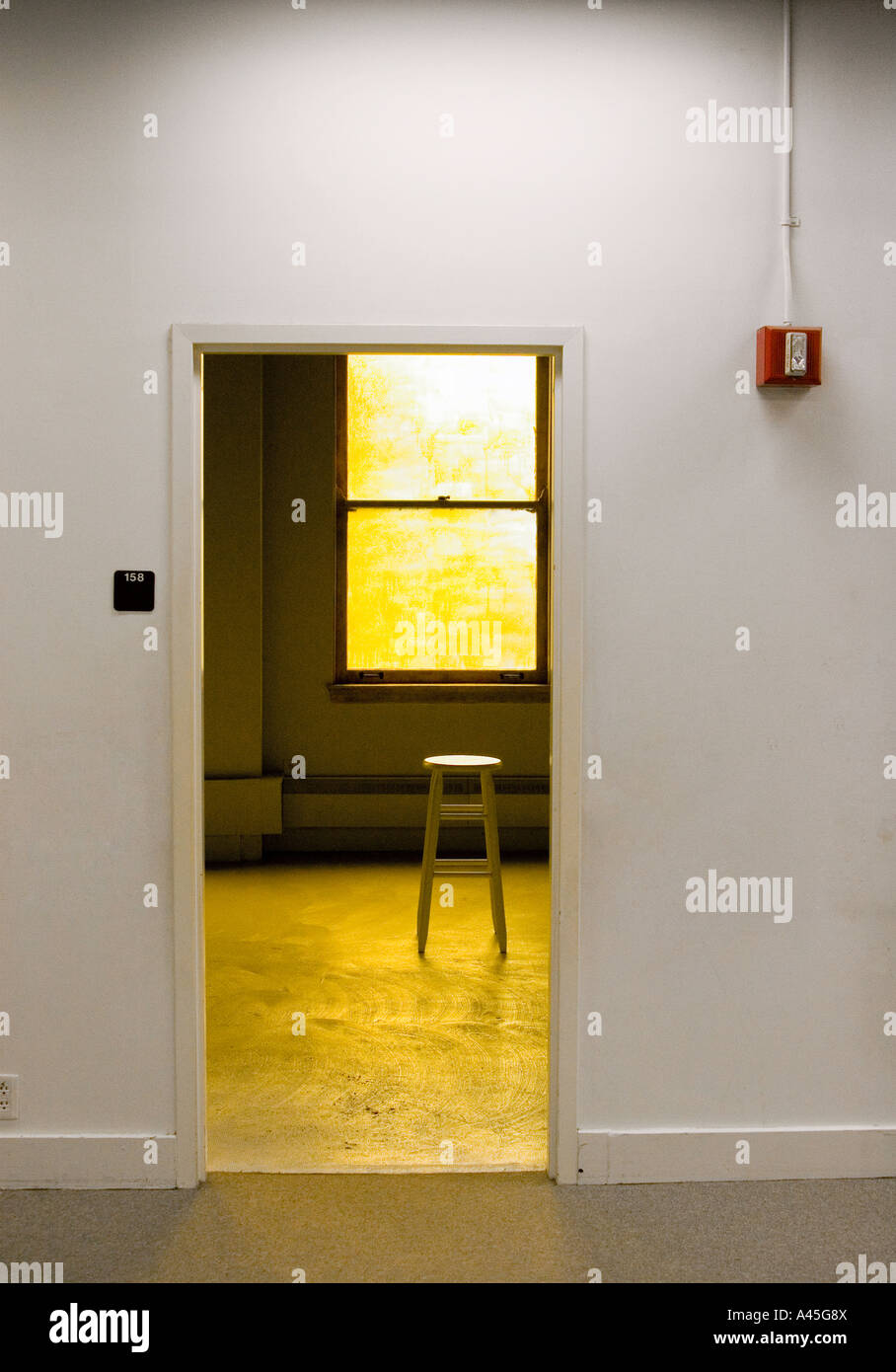 Small room with wooden stool set in warm yellow light Stock Photo