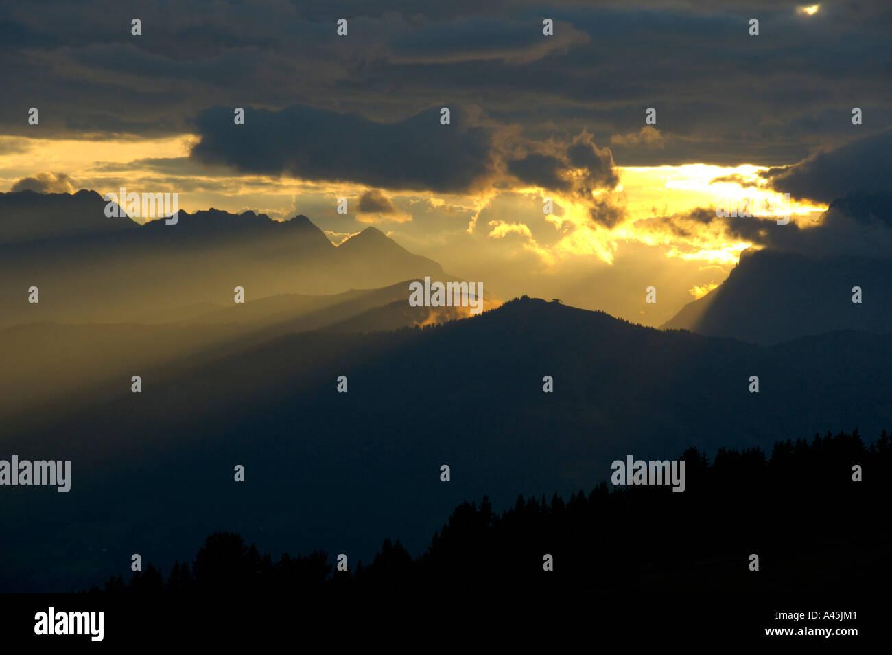 Evening sky yellow sunrays shine through dark skies Haute-Savoie France - Stock Image