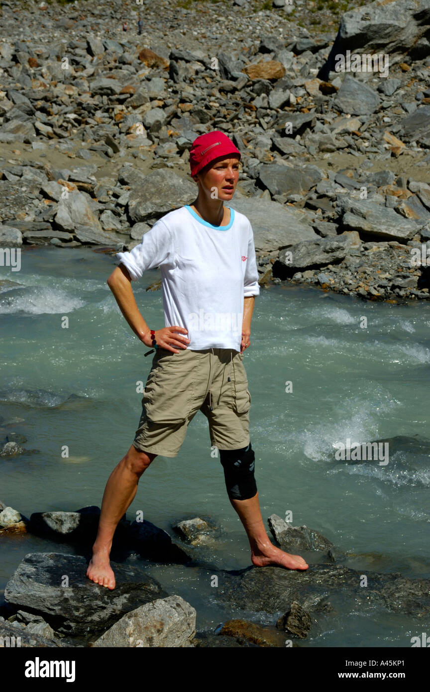 Young woman stands lofty and barefoot in icecold water of Glacier de Bionnassay Haute-Savoie France - Stock Image