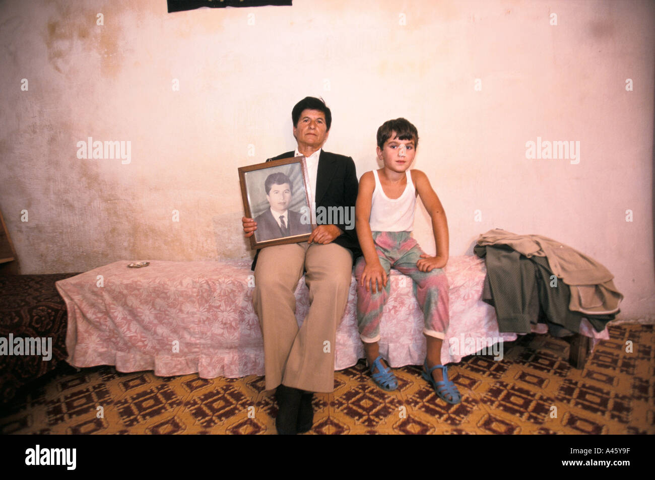 Avowed virgin Selman Brahim holds a photograph of her younger self with her grandchild in a house in Skhoder, Albania - Stock Image