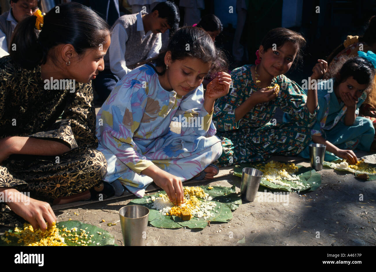 INDIA South Asia Himachal Pradesh Kulu Girls eating from banana leaves with their hands at meal during country wedding - Stock Image