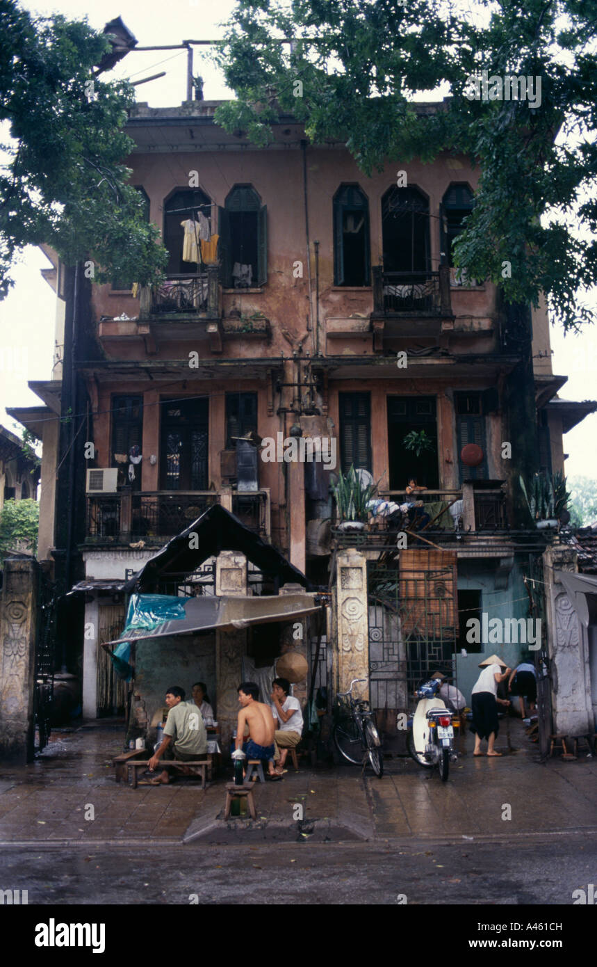 VIETNAM North South East Asia Hanoi Decayed French Colonial Style Residential Buildings With People Sheltering From The Rain