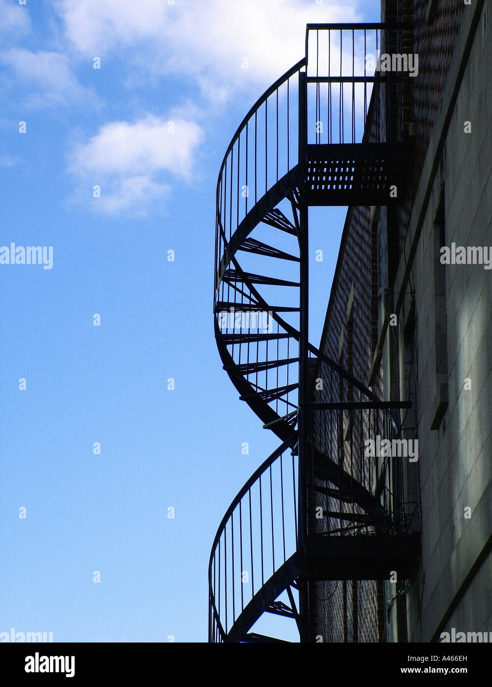 Spiraling fire escape with blue sky background - Stock Image