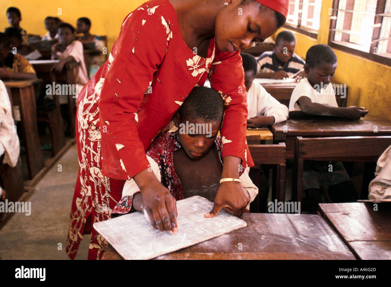 A child is helped to read by a teacher in a school run by the Youth Alive project in Tamale, Northern Ghana - Stock Image