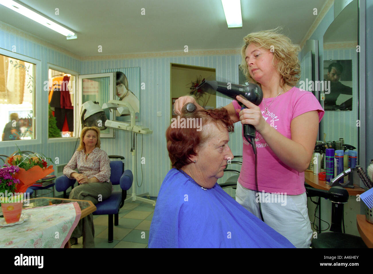 Polish hair dresser blow-dries hair of a German client, Slubice, Poland - Stock Image